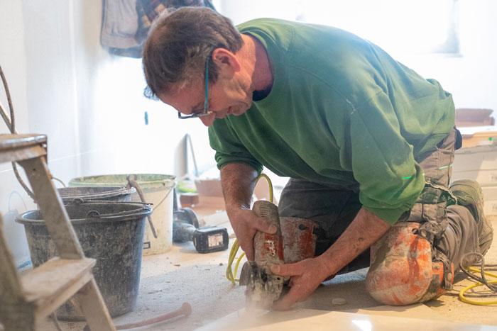 Fliesen Wöllert Meisterbetrieb | Handwerker des Betriebs Wöllert beim zuschneiden von Fliesen