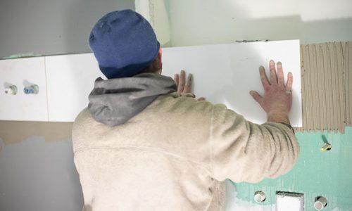 Fliesen Wöllert Meisterbetrieb | Handwerker des Betriebs Wöllert beim verlegen von Fliesen